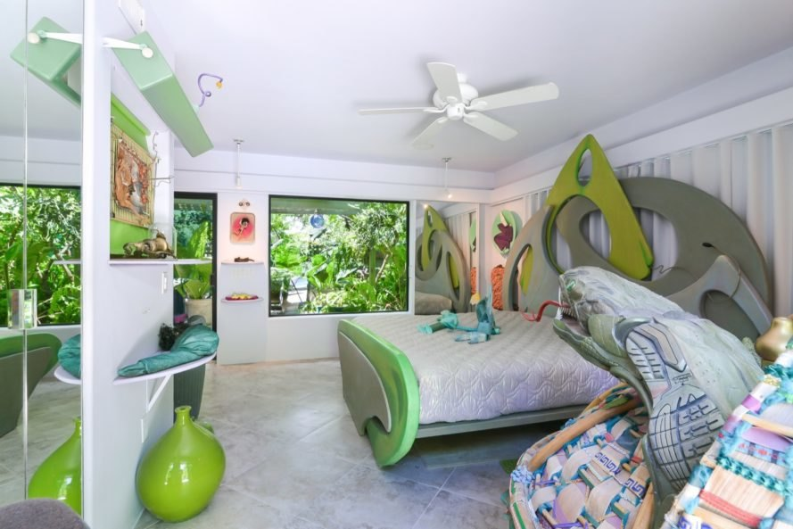 white bedroom with sculptural green bed and green art