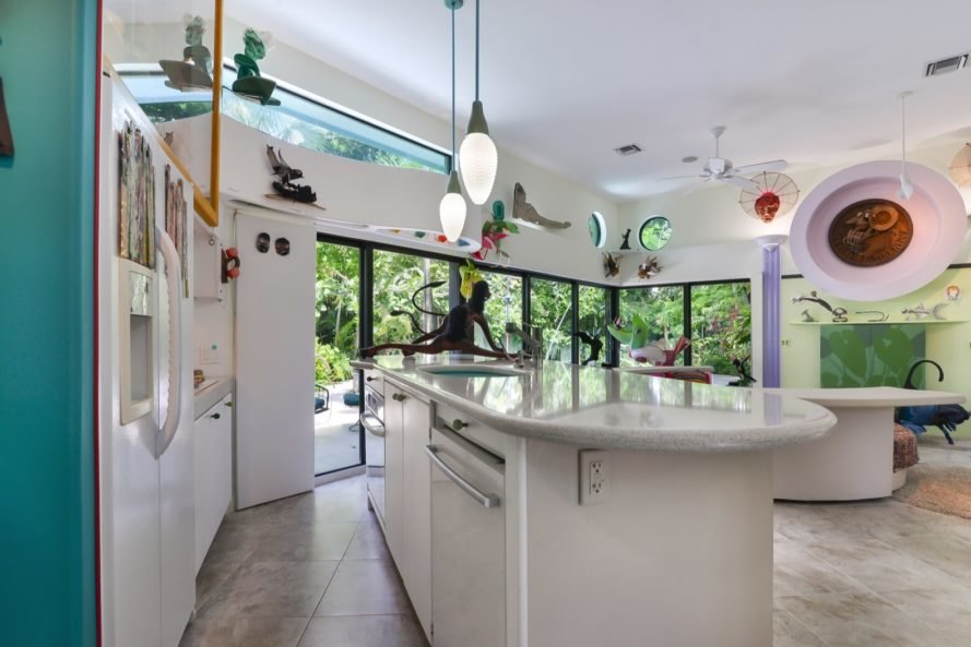 white kitchen island facing room with glass walls