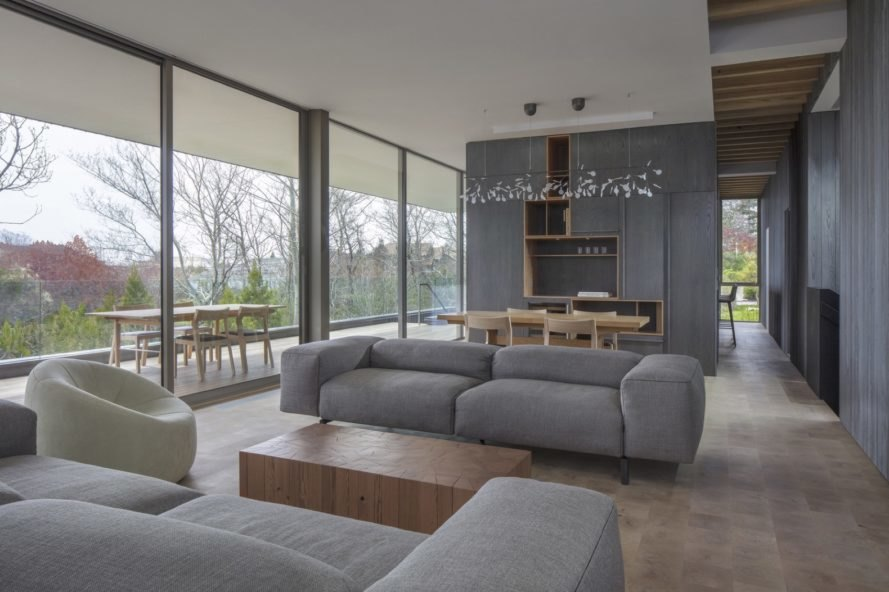 gray living area with gray couch and large windows