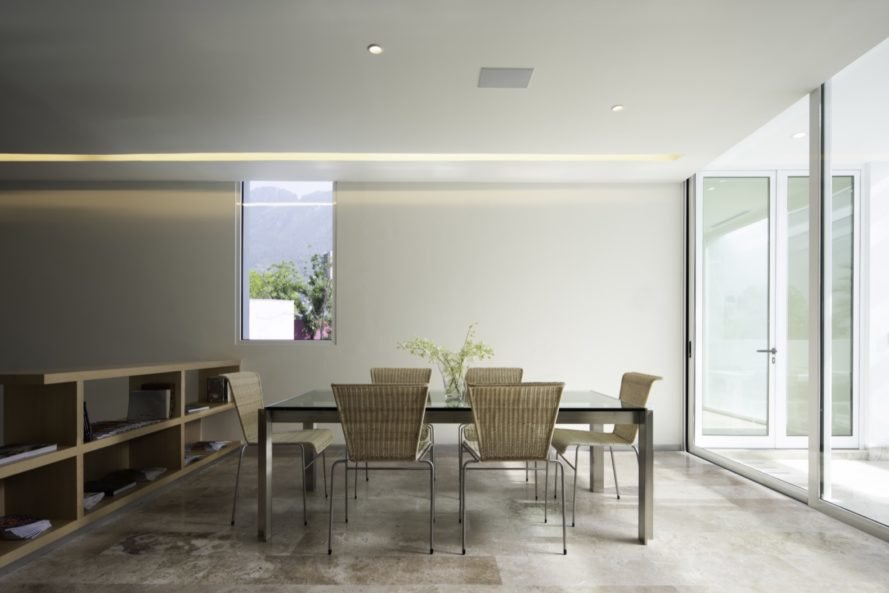 beige dining area with glass table and beige chairs