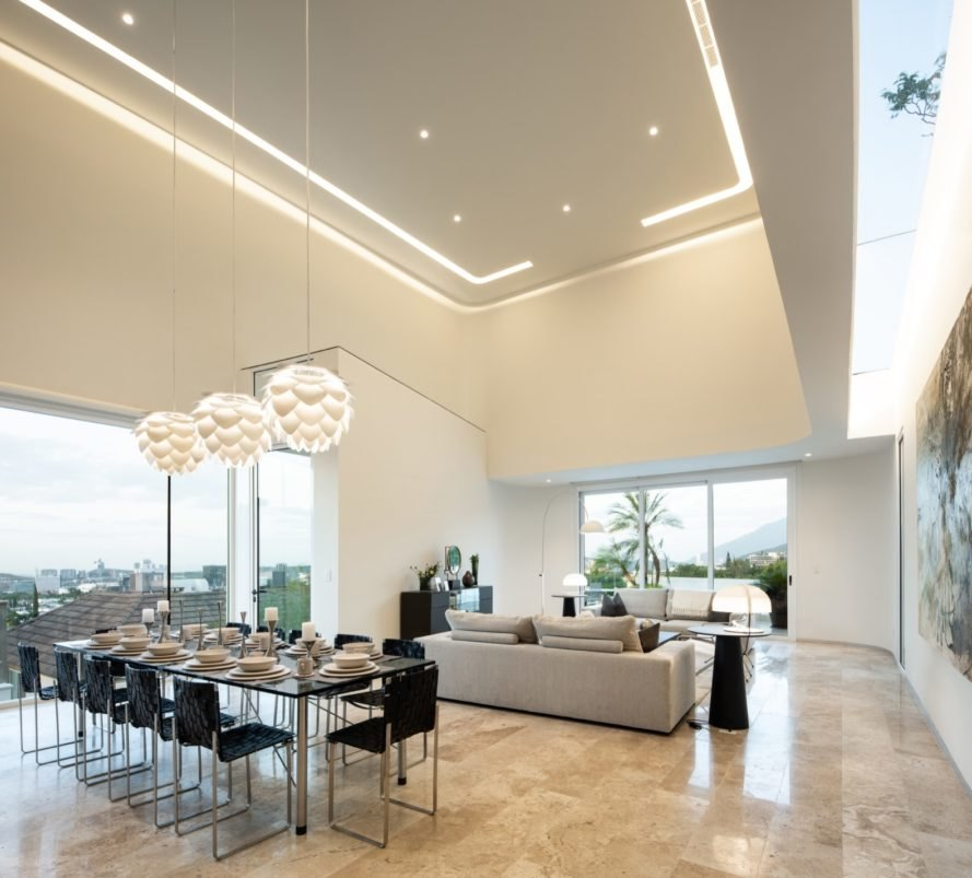 white room with double-height ceiling and glass walls, beige couches and a long glass dining table with black chairs