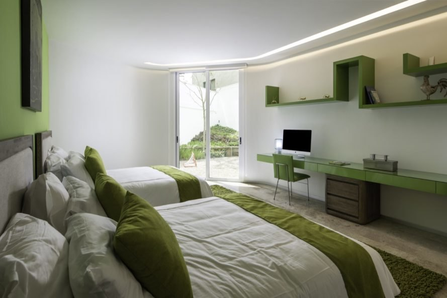 green and white bedroom with two double beds with white and green bedding and a long green desk
