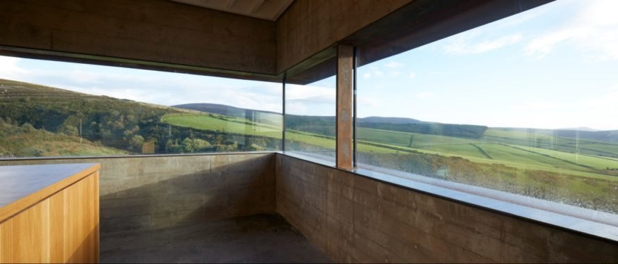 large windows with views of green rolling hills