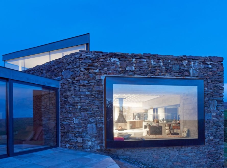 stone home with large glass windows