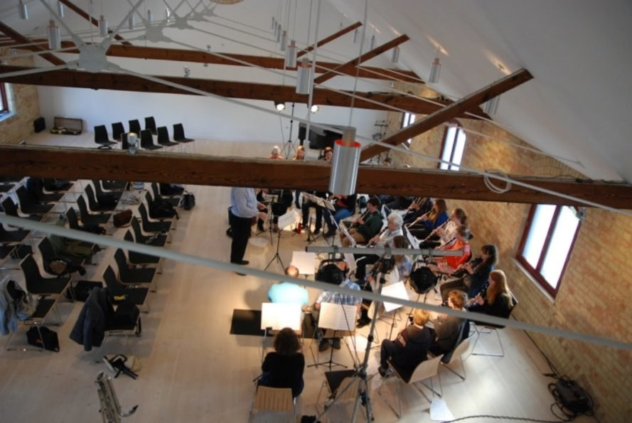 band playing instruments in white room with wood ceiling beams
