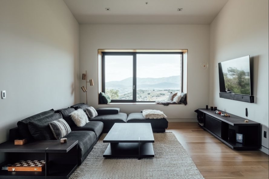 living space with black sofa and large window
