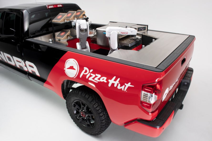 a red and black pickup truck with a pizza kitchen in the back