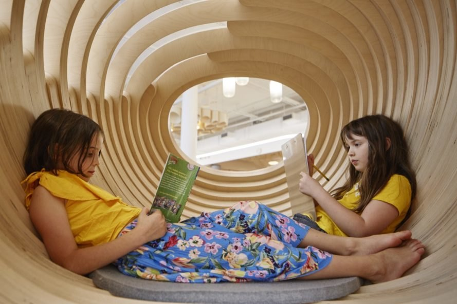 two kids reading books in a round timber structure