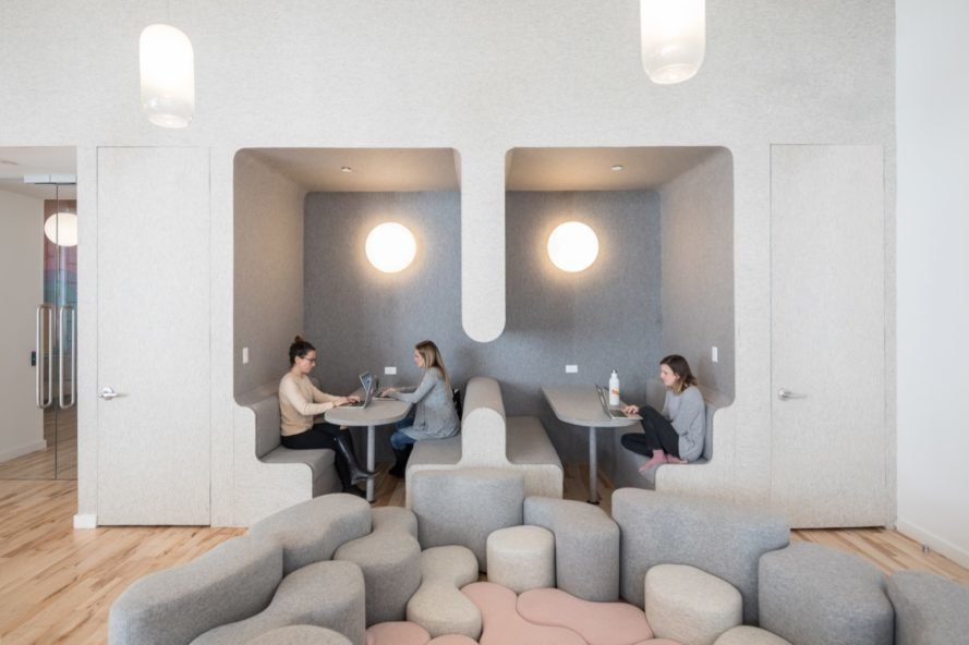 adults working in gray room with curvy furniture