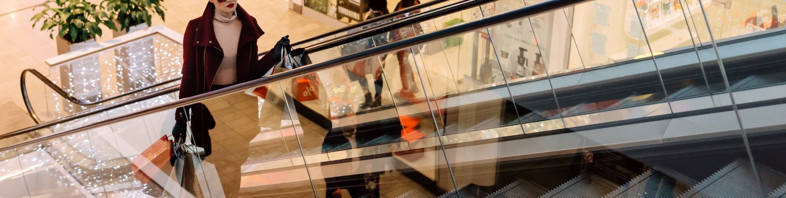 woman with shopping bags on escalator in mall