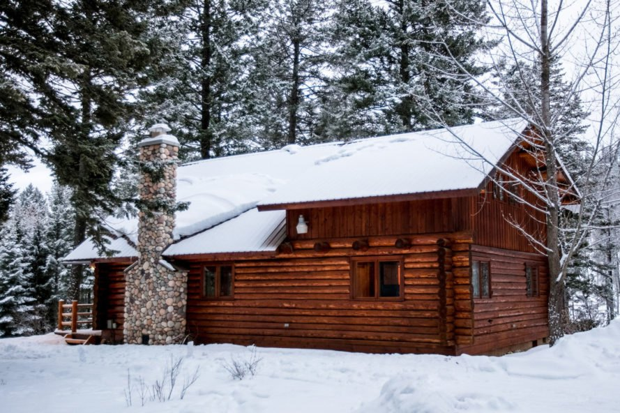 log cabin with brick chimney in snowy landscape