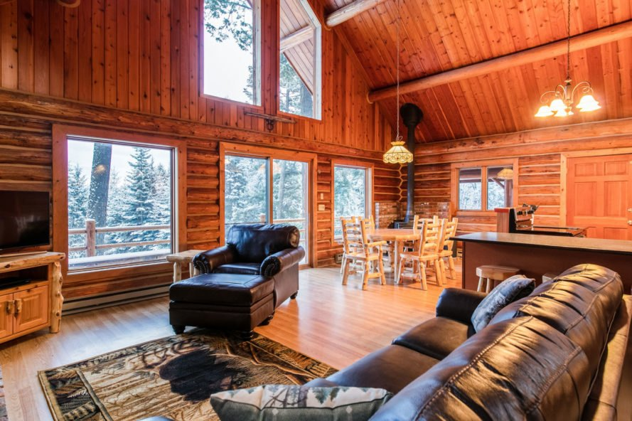 inside of log cabin with high pitched ceilings and large glass windows
