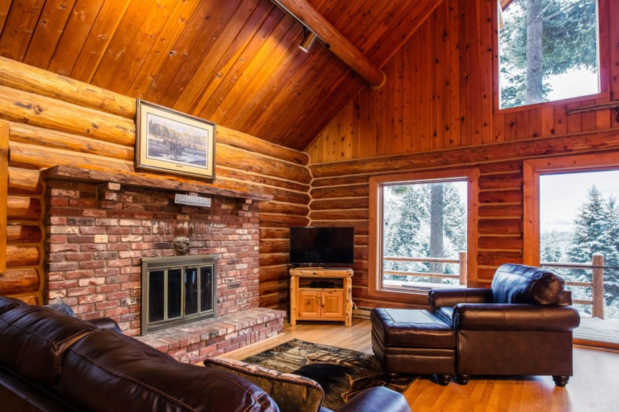 interior of log cabin with dark leather furnishings and brick fireplace