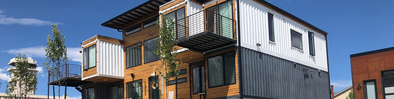shipping container home painted white and black with wood paneling