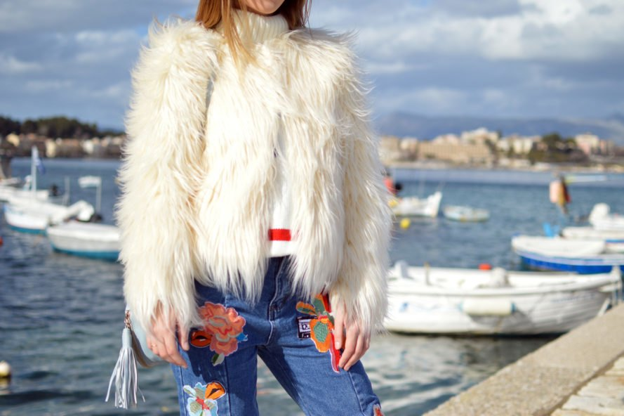 person wearing white fur coat by the beach