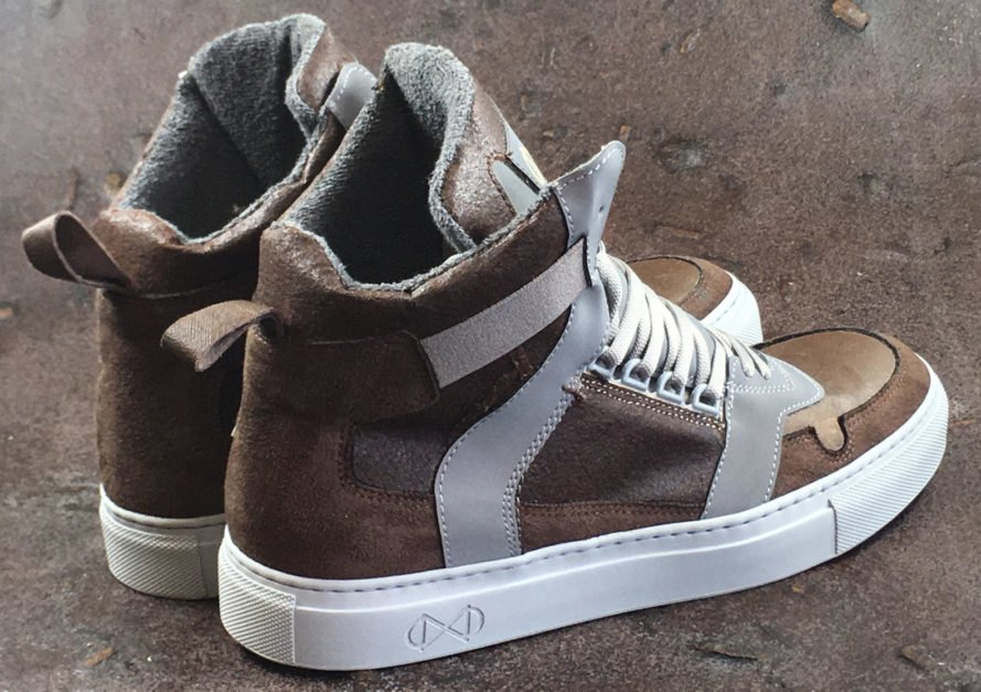 back of a pair of two-toned brown vegan leather high-top sneakers