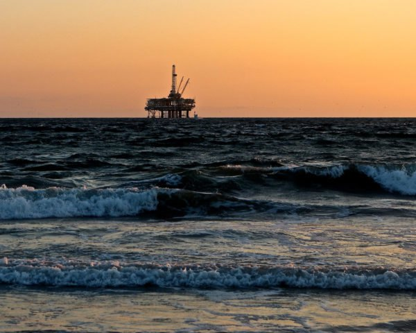 silhouette of oil rig at sea