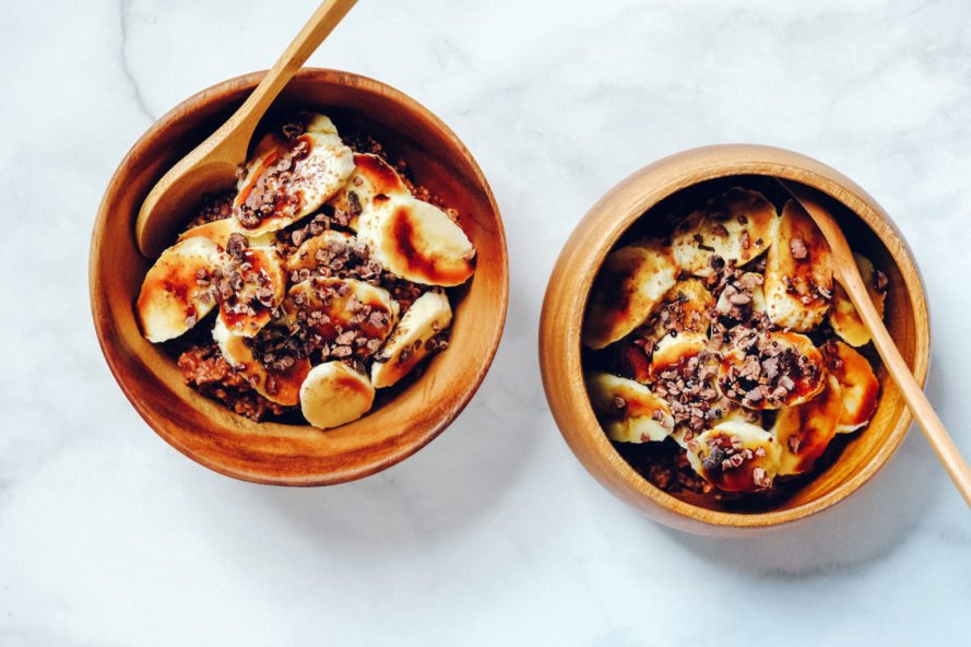 wooden bowls of oatmeal and bananas