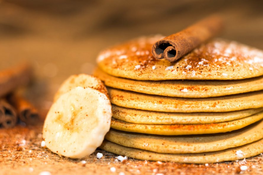 stack of pancakes topped with cinnamon and bananas