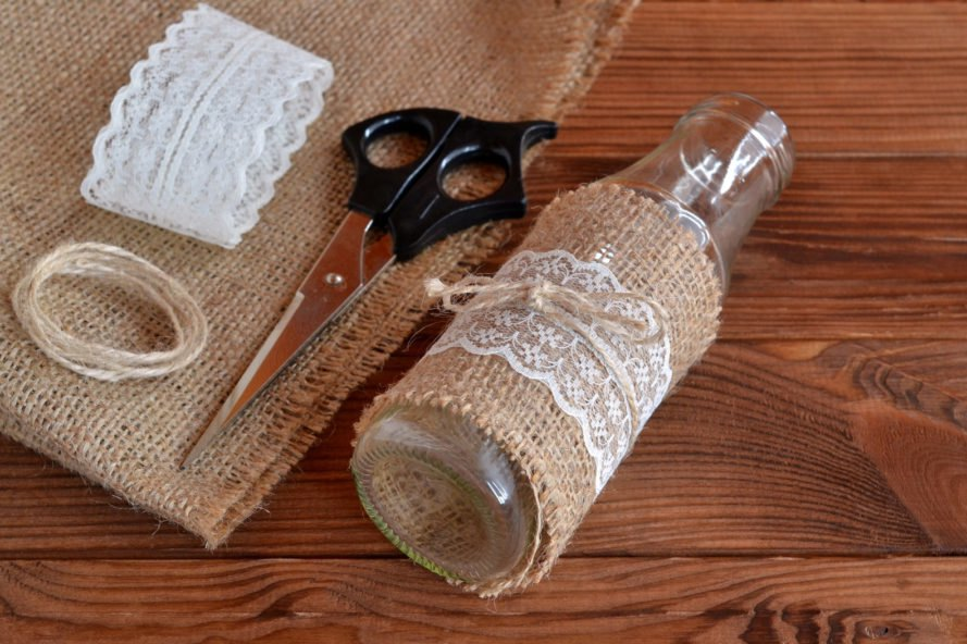 old glass bottle wrapped in burlap, lace and twine near pair of scissors
