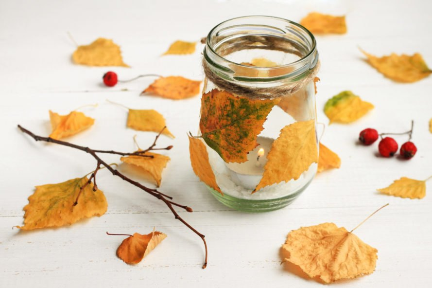 glass jar wrapped in leaves and surrounded by leaves