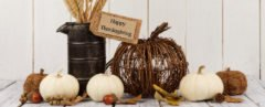 pumpkins, tin container of wheat, twig pumpkin and leaves on a white table