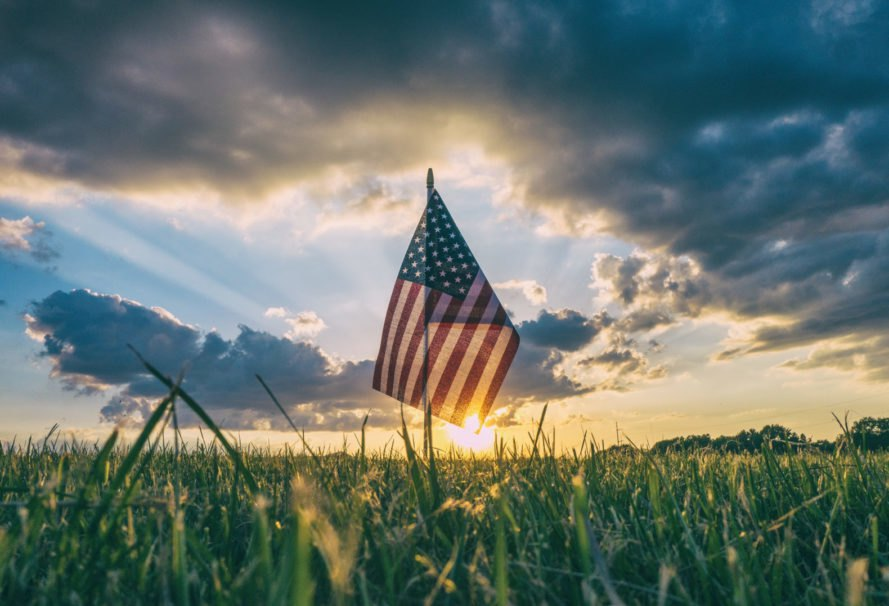 American flag in grass at sunset