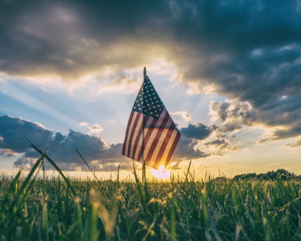 American flag in the grass at sunset
