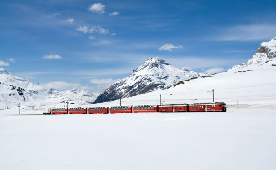 Red train with snow covered mountains
