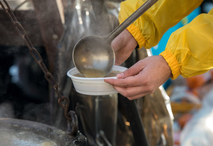Bowl of soup being poured by volunteer