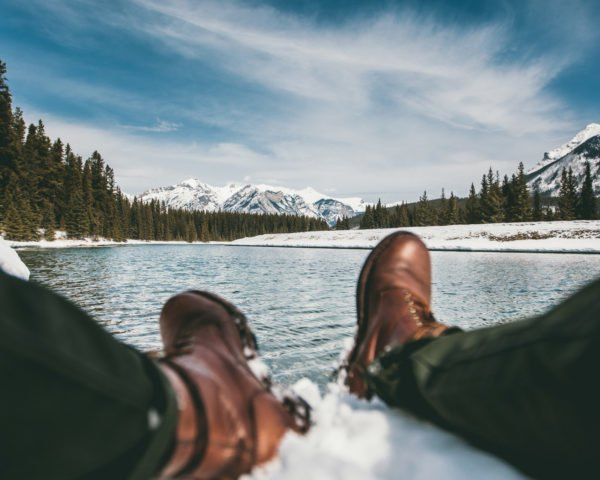 Brown boots with lake pine trees and snowy mountains
