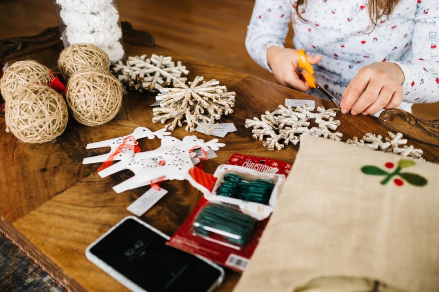 Woman making Christmas crafts on wooden table