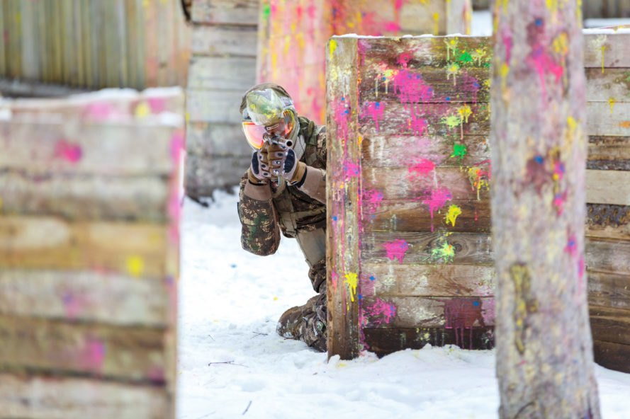 Man shooting paintball in snow covered background
