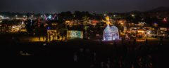 several stages and vendors with colorful lights at night