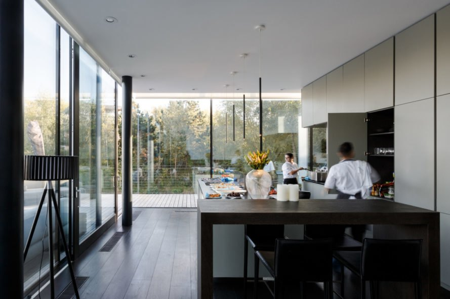 black kitchen surrounded by glass facades