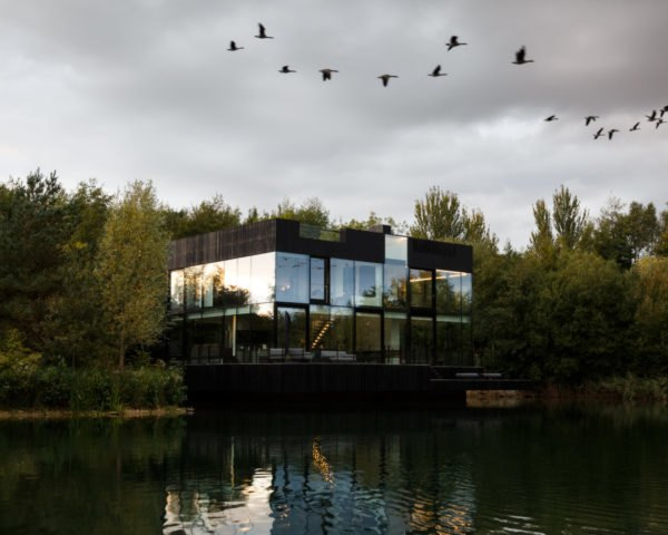 glass home on a lake with a forest in the background