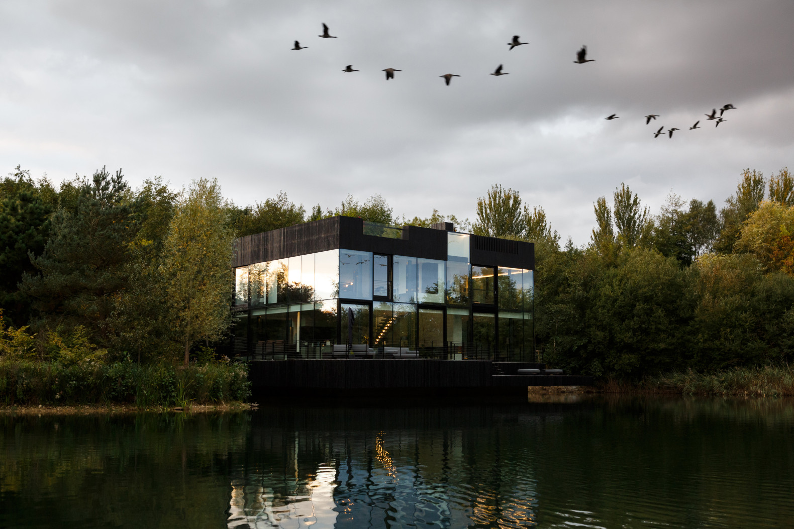 Mecanoo unveils stunning glass lake house that harmonizes with nature