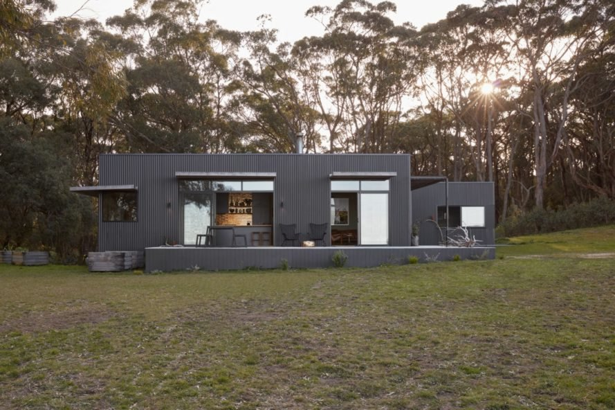 grey home with large windows surrounded by greenery