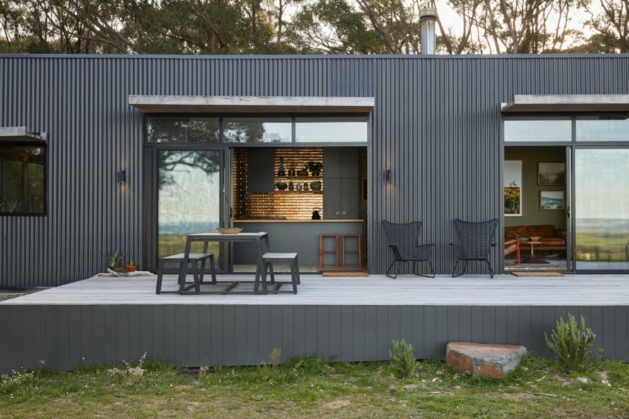 grey home with large sliding doors opened to an open-air patio