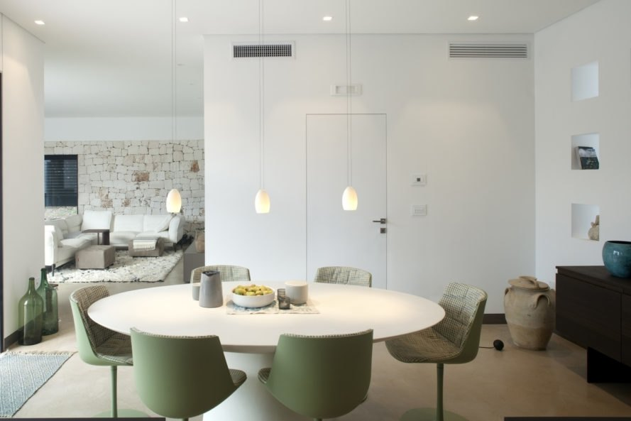 interior dinning area of the home with green chairs and white table