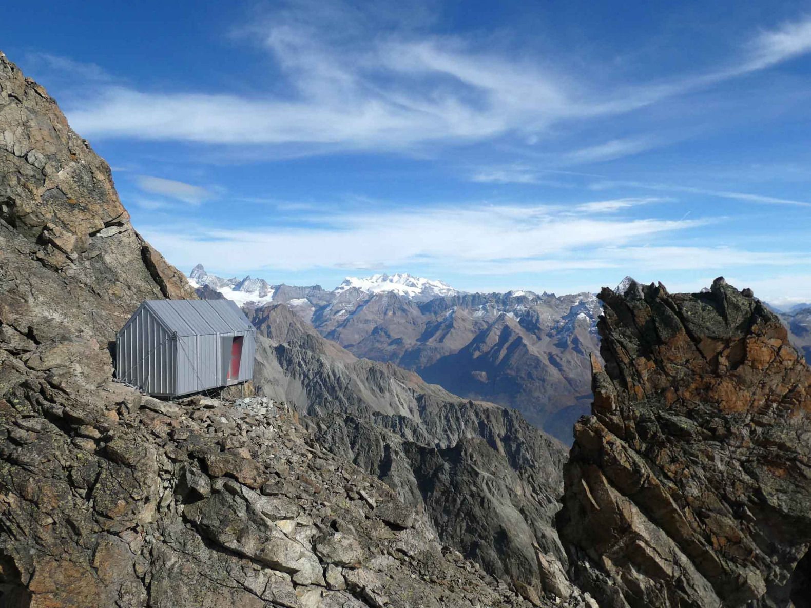 A bivouac is lightly perched on a rocky peak of the Italian Alps