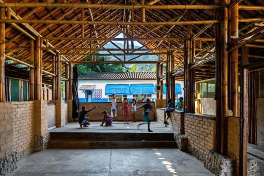 children playing inside the community bamboo buidling