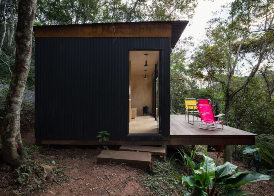 Small structure with black corrugated metal siding and front deck