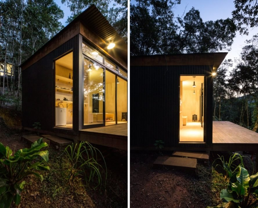 Tiny black cabin illuminated at night