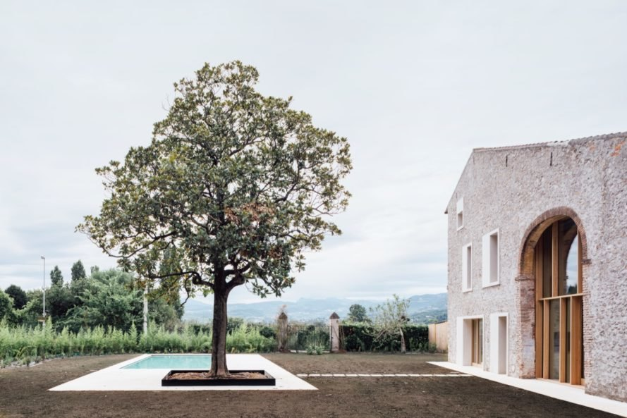 stone farmhouse with large tree beside small pool