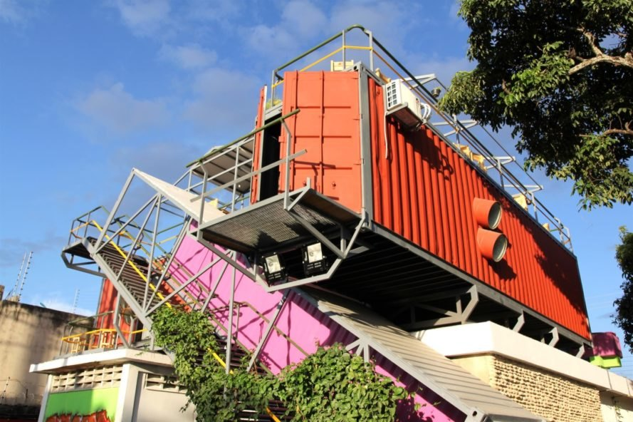 angled pink shipping container staircase leading to orange shipping containers