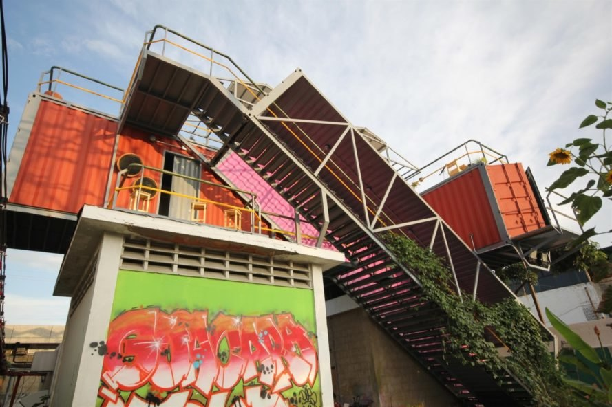 building with graffiti below stacked shipping containers