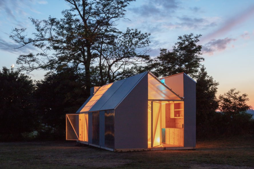 gabled cabin with transparent walls at night