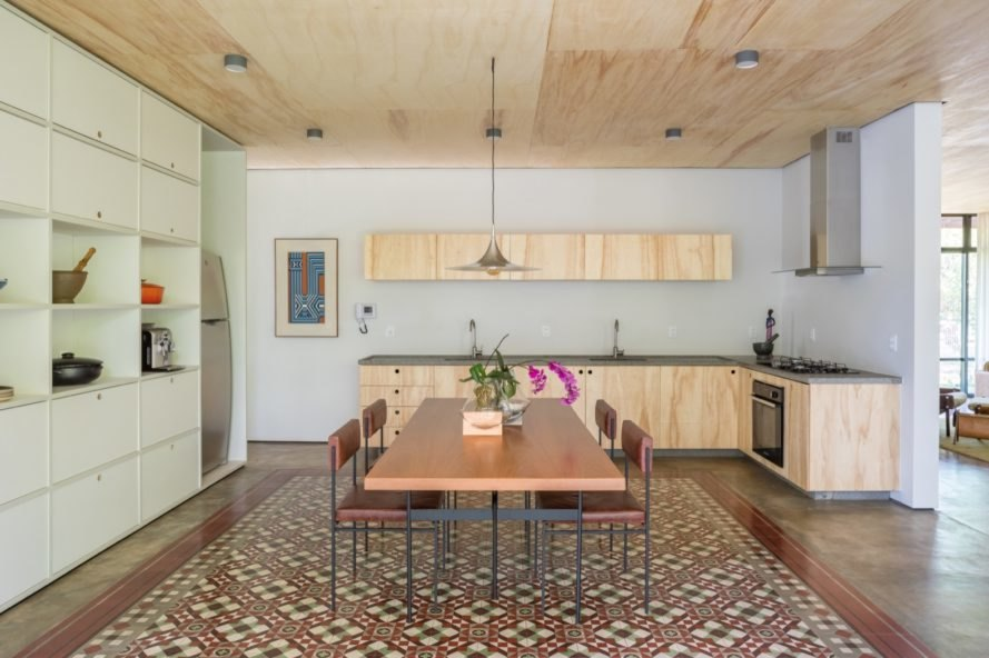 kitchen filled with light with wood cabinets and wood table and intricate floor tile design