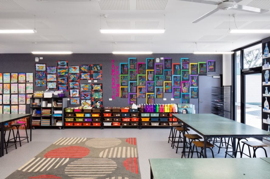 classroom with dark walls covered in neon art